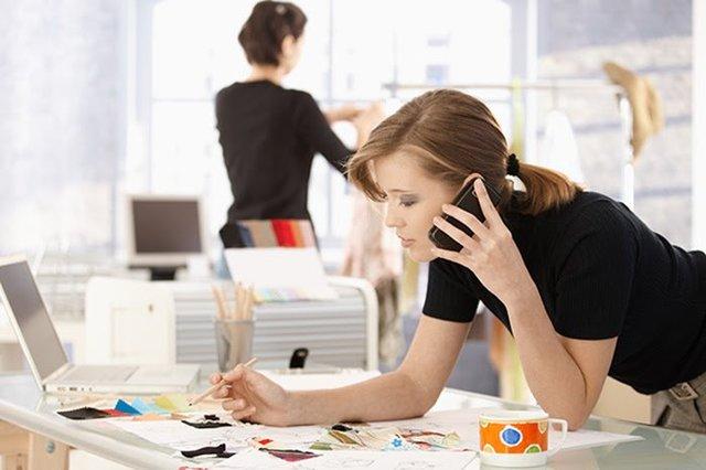 Telefonierende Frau, die über einen Schreibtisch voll mit Zetteln gebeugt ist. Frau hält einen Bleistift in der rechten Hand und ihr Handy in der linken Hand am Ohr. Im Hintergrund sind Büroräume zu erkennen und eine Kollegin. Am Tisch selbst befindet sich zusätzlich zu den vielen Zetteln ein Laptop, ein Glas voll mit Stiften und eine bunte Tasse.