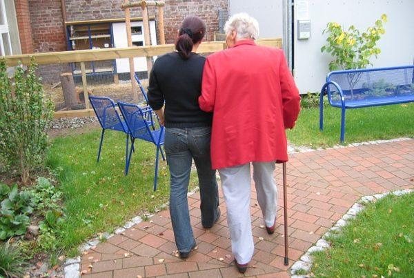 ältere Frau mit Gehstock, die sich bei einer jüngeren Frau unterm Arm eingehakt hat. Beide gehen auf einem Weg im Garten.