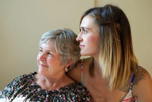 ältere Frau an die Schulter einer jüngeren Frau gelehnt. Beide schauen in die selbe Richtung und lächeln.