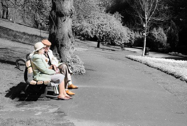ein altes Ehepaar auf einer Bank im Park sitzend. Bild ist schwarz-weiß, nur Personen sind in Farbe. Tragen beide einen Hut und pastellfarbene Kleidung.