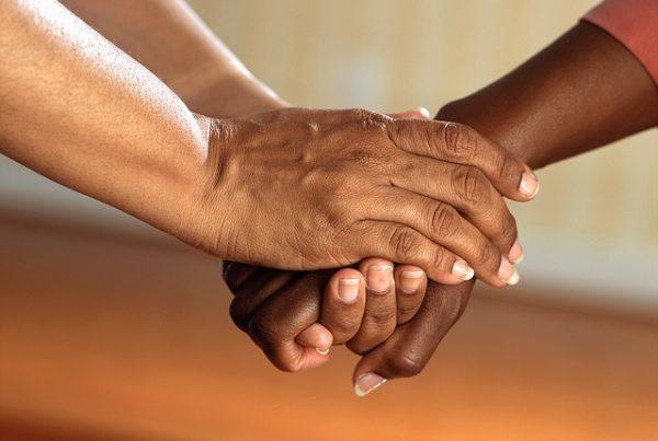 Hände von zwei Personen. Die eine Person nimmt mit ihren beiden Händen die Hand der zweiten Person und hält diese.