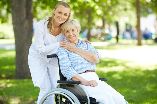 Elsner Pflege Altenpflegerin mit Frau im Rollstuhl