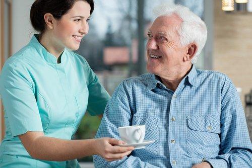 Pflegekraft, die einem älteren Herren eine Tasse Tee hinstellt. Beide lachen sich an.