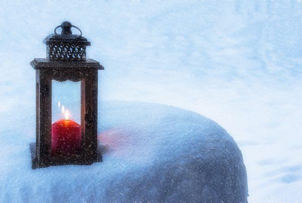 Laterne mit Kerze, die auf einer Schneebedeckten Erhöhung steht.