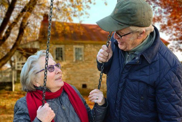 ältere Frau auf einer Schaukel in der Natur. Daneben ein älterer Herr, der die Schaukel an einer Kette festhält. Beide sehen sich an und lachen