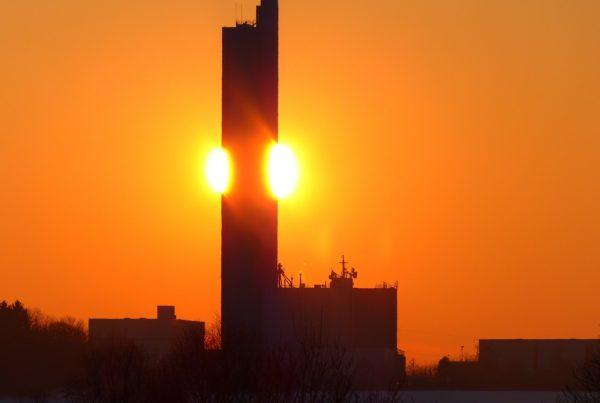 rot-oranger Himmel mit Sonnenuntergang im Hintergrund. Häuserumrisse im Vordergrund.