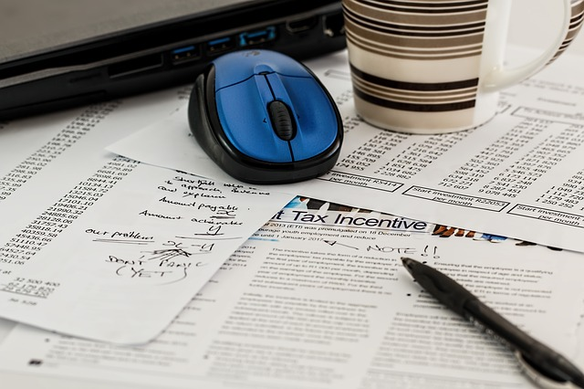 Zettel verstreut auf einem Tisch. Auf den Zetteln liegt ein Stift und ein Laptop mit zugehöriger Maus. Außerdem steht eine Tasse neben dem Laptop.