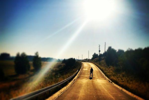 Straße mitten in der Landschaft. auf der eine Person steht. Sonne scheint stark.